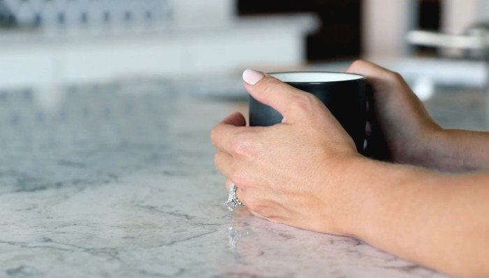 woman's hands holding coffee mug on stone countertop