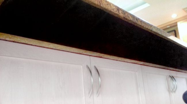 underside view of stone countertop overhang with heating mat attached