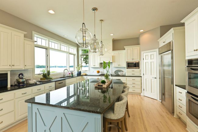 modern kitchen interior with wide walking space near stone countertop and white cabinets