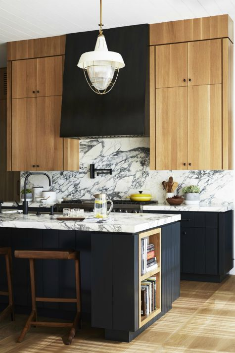 kitchen interior with black and white stone countertop and backsplash with beige and black cabinets and vent hood