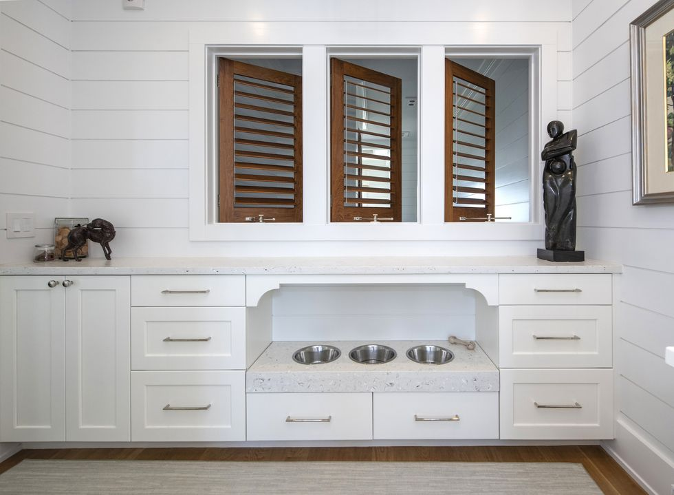 all white kitchen pantry area with build in dog bowls and brown stained shutters looking into another room