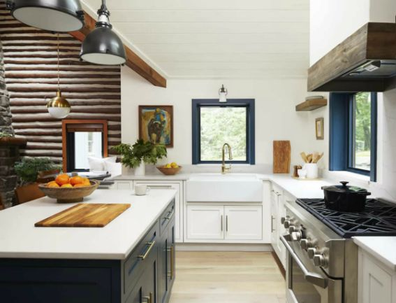 modern kitchen with stone countertop and stainless appliances leading into a cabin style living room
