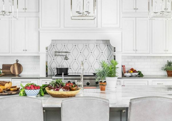 all white kitchen interior with stone countertop and assorted fruits on top