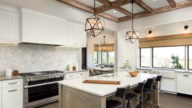 modern kitchen interior with white stone countertop and hanging metal chandeliers and stainless steel oven and stove
