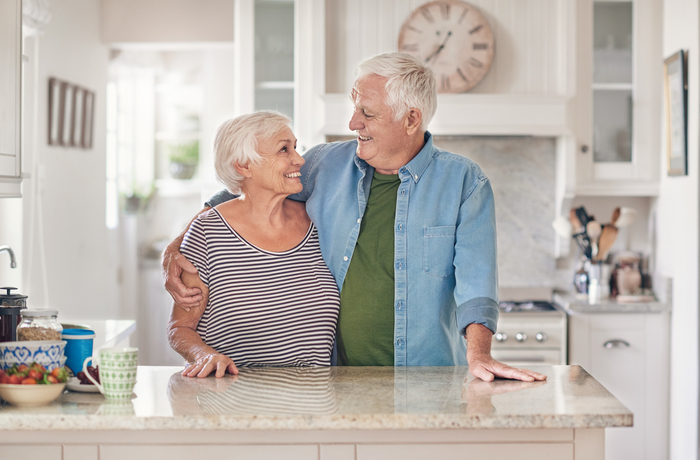 elderly couple embracing one another in a kitchen area