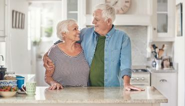 elderly man and woman embracing one another in kitchen area