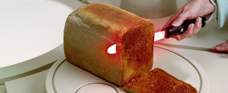 image of person holding heated bread knife while cutting and toasting a loaf of bread at the same time
