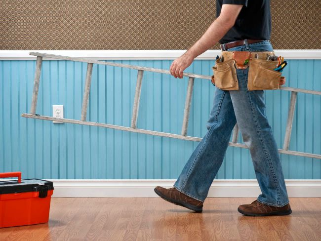 man with tool belt on waist carrying ladder through a house