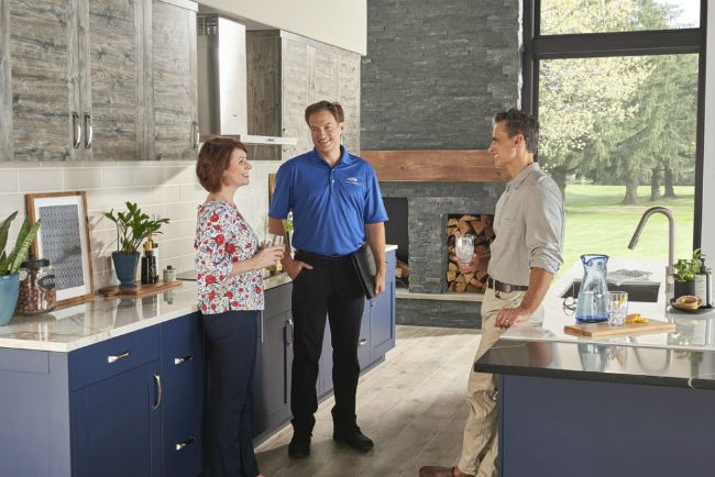 two men and a woman standing and talking in a modern kitchen area