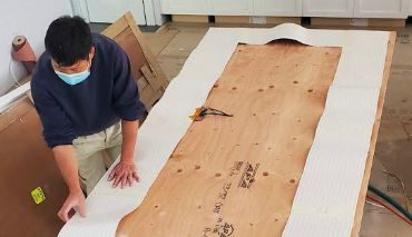 man attaching heating pad to the underside of a countertop