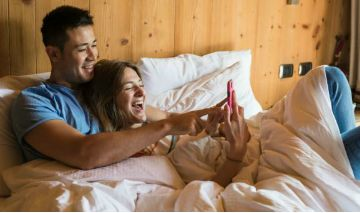 man and woman laying in bed looking at phone screen smiling