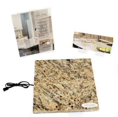 sample size stone countertop cutout connected to FeelsWarm heating pad next to company brochure