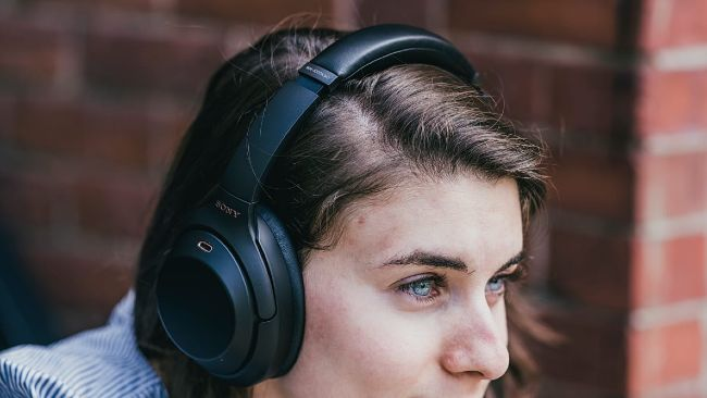 woman with headphones on looking intensely into the distance