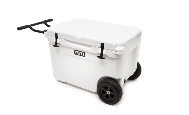 Yeti brand cooler with a tow bar and wheels on a white background