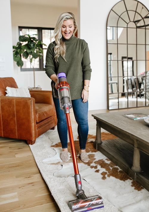 woman holding vacuum over rug in a house