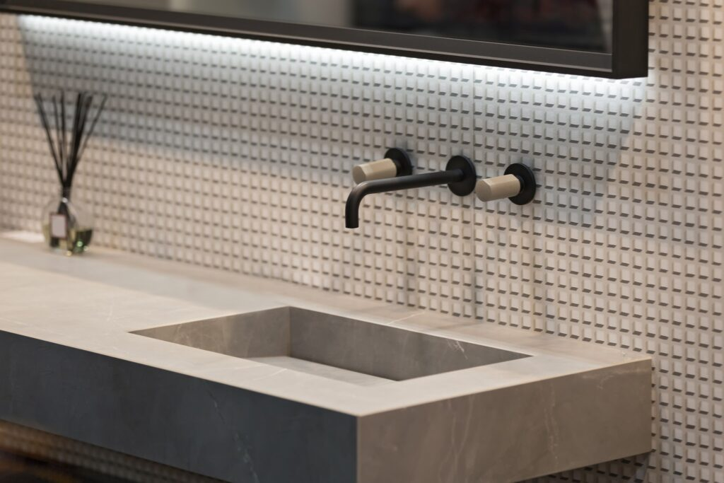 An industrial bathroom with stone countertop.A luxury guest bathroom idea is including FeelsWarm heating components.