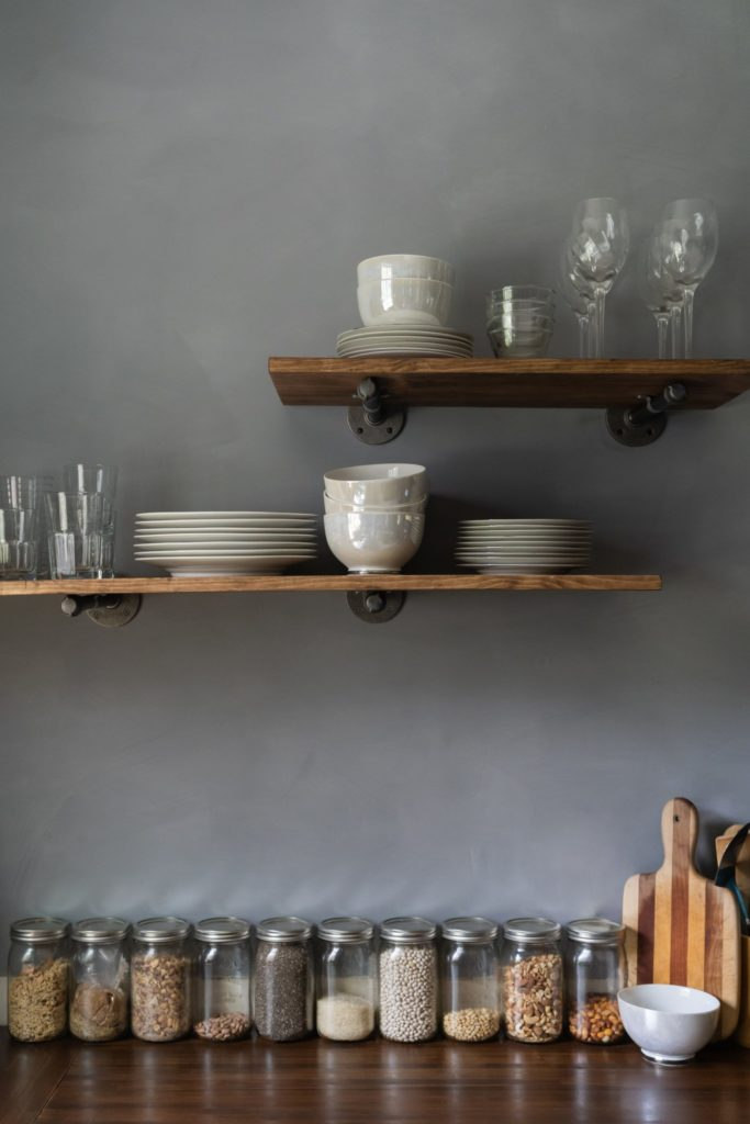 Floating shelves stacked with dishes in an industrial kitchen
