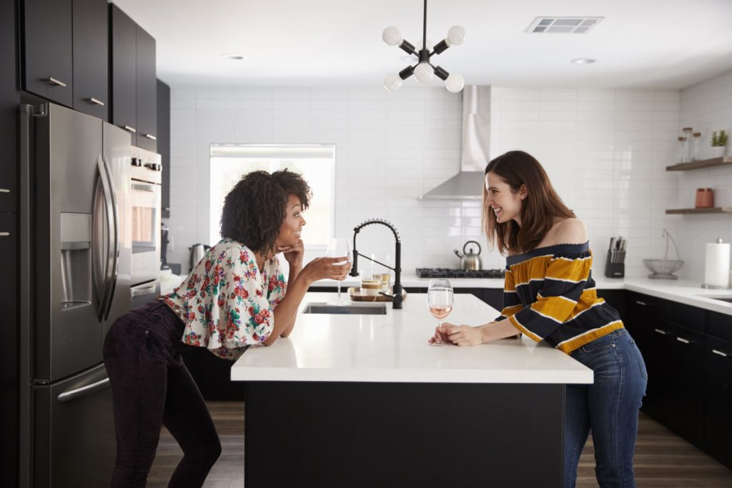 Two women chatting and having wine around an industrial-style kitchen island that is heated with FeelsWarm heating mats.
