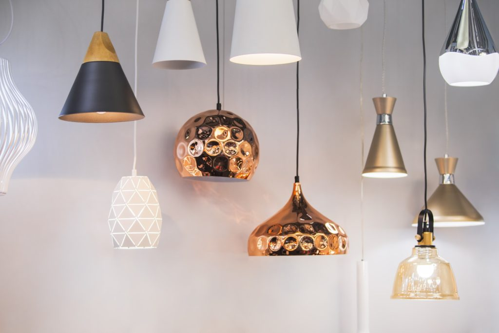 Various pendant lights of various shapes and colors that would warm up an industrial kitchen.