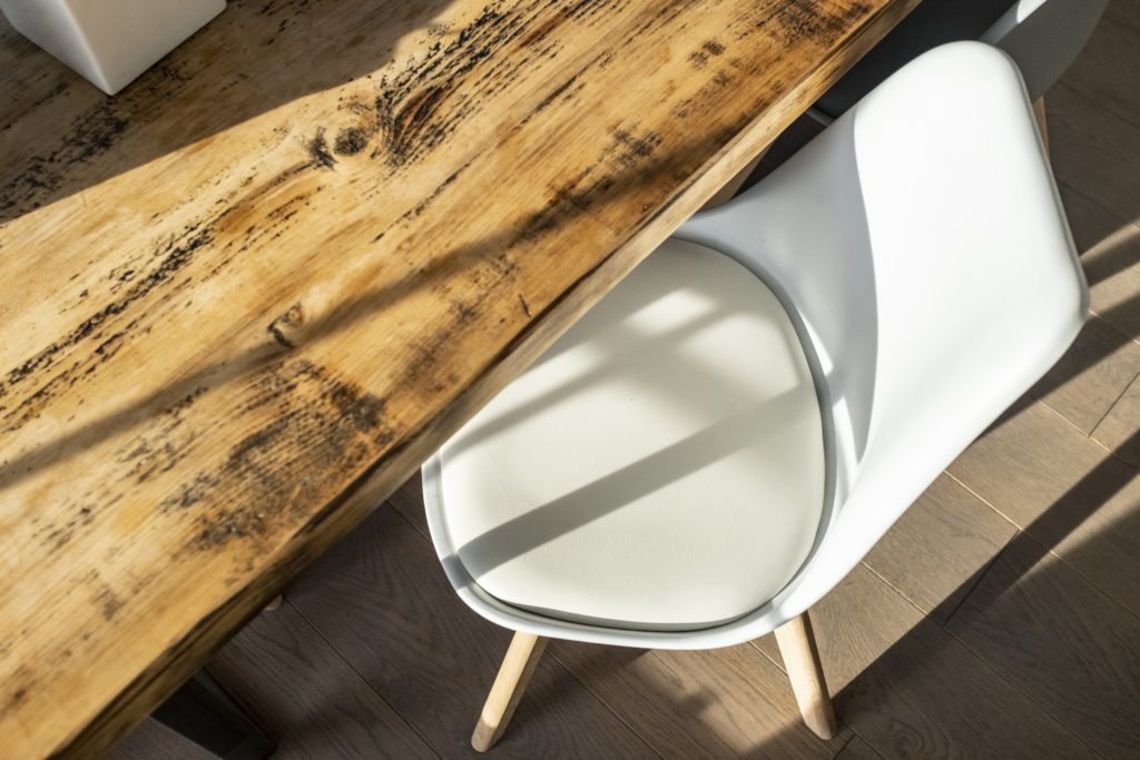 A reclaimed wood table with a white mid-century modern egg chair.
