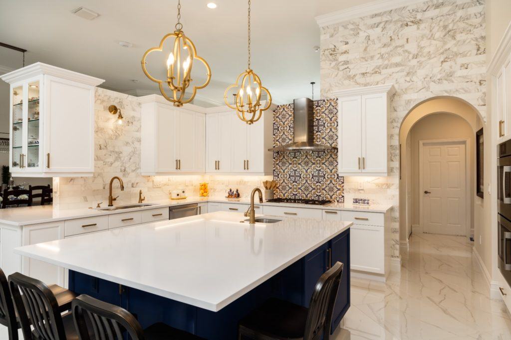 A mediterranean style kitchen with unique backsplash and marble counters.